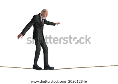senior man walking a tightrope isolated on white - stock photo