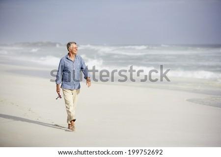 Senior man walking on beach - stock photo