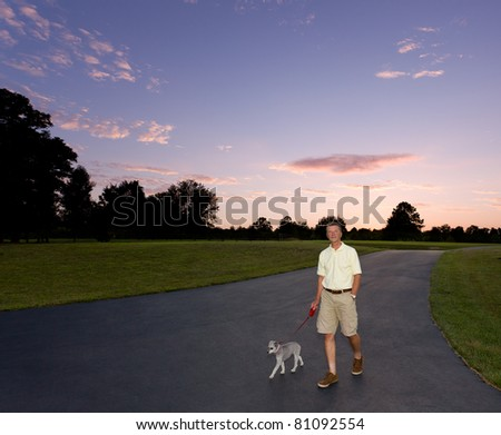 Senior man walking small puppy at dusk as the sun sets behind them - stock photo