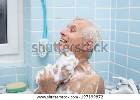 Senior man washing his body with soap in bath. - stock photo