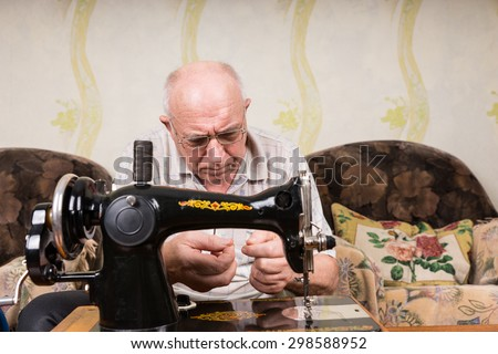 Senior Man Wearing Eyeglasses in Deep Concentration Threading Needle of Old Fashioned Manual Sewing Machine at Home in Living Room - stock photo