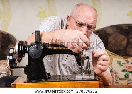 Senior man wearing glasses sitting in his living room using a sewing machine carefully threading the needle with thread