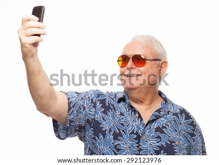 Senior man wearing loud hawaiian shirt on white background taking photo selfie with mobile phone. - stock photo