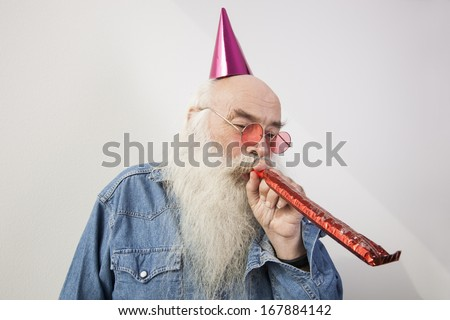 Senior man wearing party hat while blowing horn against gray background - stock photo