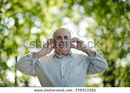 Senior man with a blissful expression stands stands outdoors in a wooded garden listening to music on his headphones smiling in satisfaction - stock photo