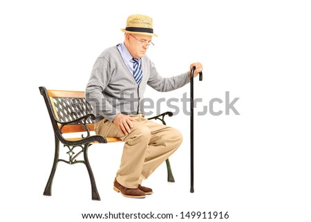 Senior man with a cane sitting on a bench isolated on white background - stock photo