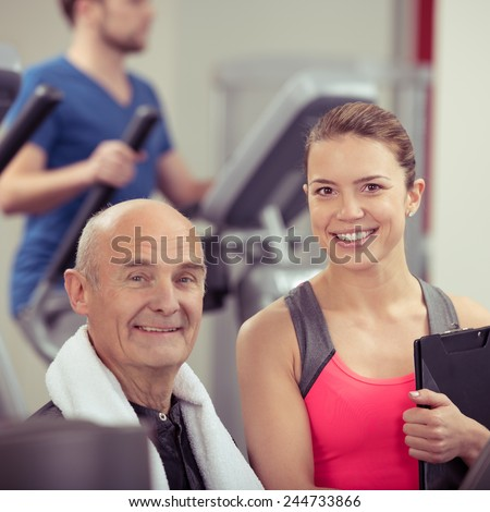 Senior man with an attractive young female trainer in a gym looking at the camera with friendly smiles in a health and fitness concept - stock photo