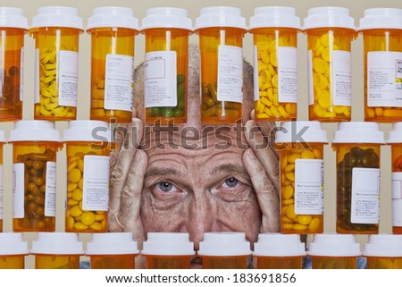 Senior man with an unhappy, depressed expression and his hands framing his face looking through an opening in rows of prescription medication. Health care cost can overwhelm many senior citizens. - stock photo
