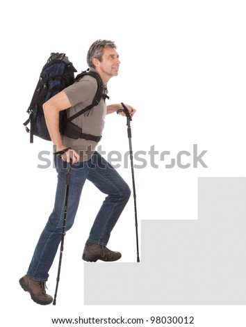 Senior man with backpack and hiking poles climbing a staircase. Isolated on white
