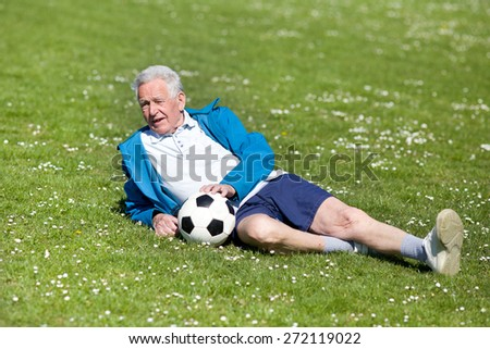 Senior man with ball  lying on grass after football match - stock photo