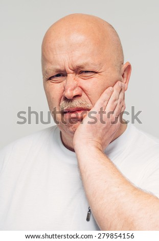 senior man with cheek soreness or tooth pain - stock photo