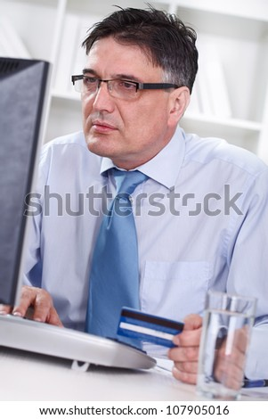 senior man with credit cart shopping over internet - stock photo