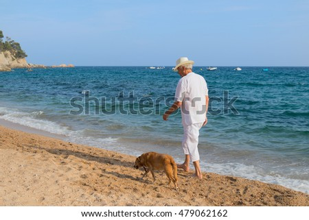 Senior man with dog in white suit walking at the beach