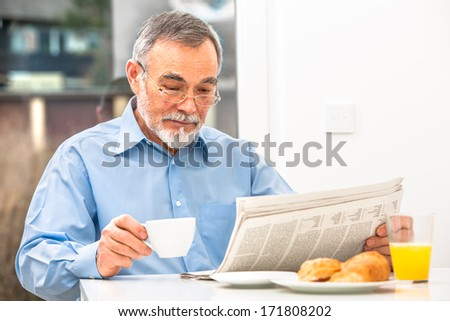 Senior man with glasses reading newspaper at breakfast