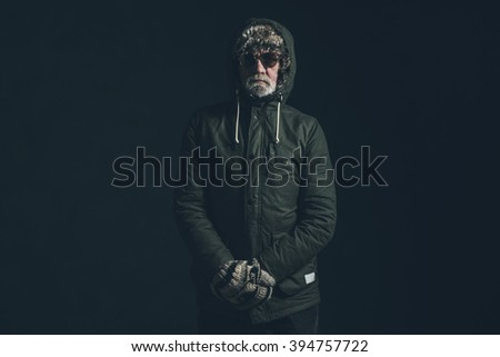 Senior man with gray beard wearing dark green winter coat with hoody.  - stock photo