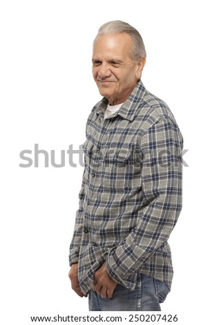 Senior man with hands in pockets and looking down against white background