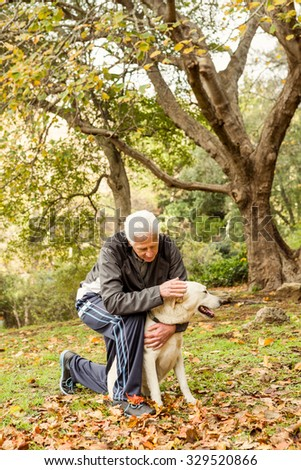 Senior man with his dog in park on an autumns day - stock photo