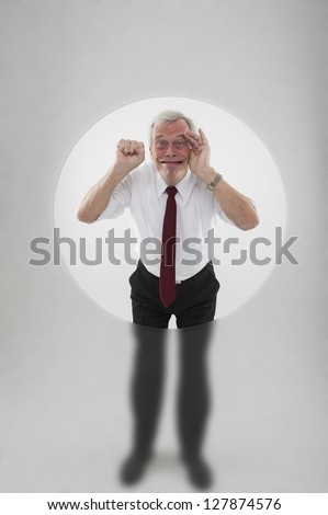 Senior man with his face pressed up against a clear hole in a frosted glass surround banging on a the glass with his fist to attract attention while smiling and grimacing in frustration - stock photo