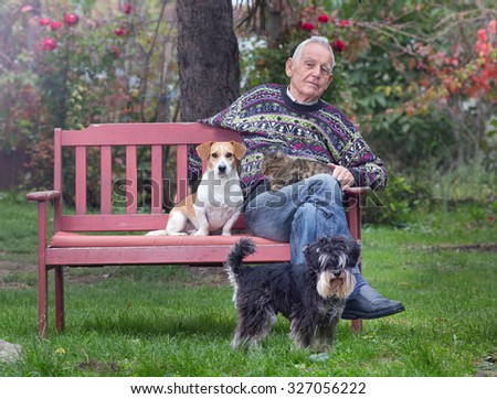 Senior man with his pets sitting on bench in the park