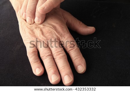 Senior man with pain on the back of his hand, copy space included - stock photo