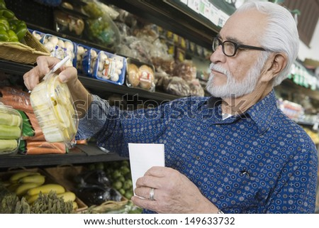 Senior man with shopping list at vegetable rack in supermarket - stock photo