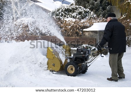 senior man with snow blower in wintertime - stock photo