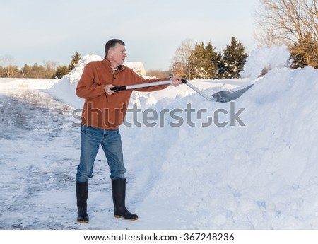 Senior man with snow shovel finishes removing snow drifts on driveway by digging out from the blizzard - stock photo