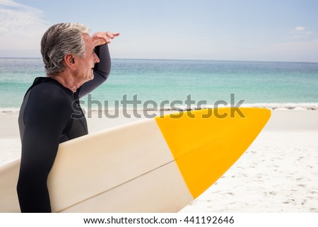Senior man with surfboard shielding eyes at beach on a sunny day - stock photo