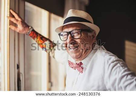 Senior man with tattoo smiling and looking at camera  - stock photo