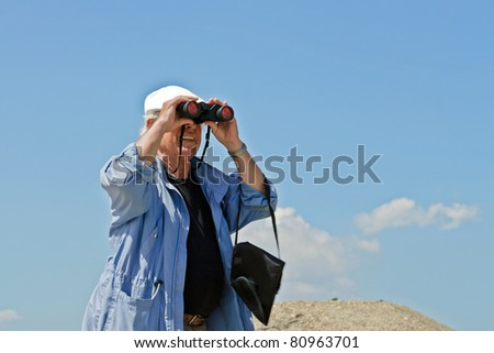 Senior man with white hat and binoculars in nature on summer day.