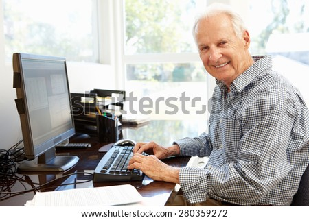 Senior man working on computer at home - stock photo