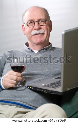 Senior man working on laptop with a glass of wine