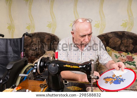 Senior Man Working On Needle Point Wall Hanging and Seated in front of Old Fashioned Manual Sewing Machine in Living Room at Home - stock photo