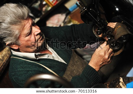 Senior man working with old machine in his own workshop - stock photo