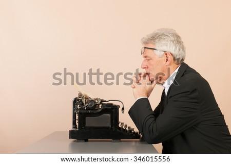 Senior man writing with Antique black typewriter - stock photo
