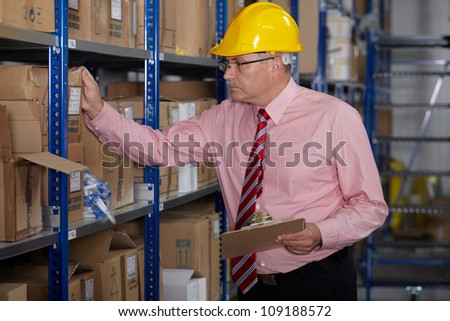 Senior manager check stock in the warehouse, wear yellow hardhat - stock photo