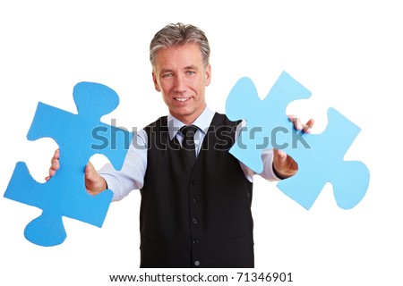 Senior manager holding two oversized blue jigsaw pieces - stock photo