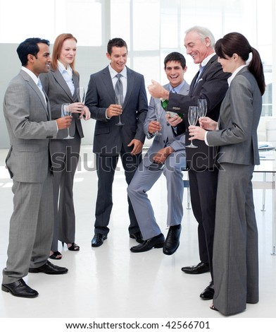 Senior manager opening a bottle of Champagne to celebrate a success with his team in the office - stock photo