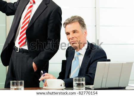 Senior Manager or boss in meeting contemplating new strategy - stock photo