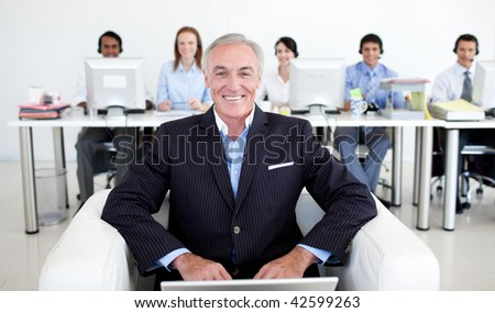 Senior manager using a laptop with his team in the background - stock photo