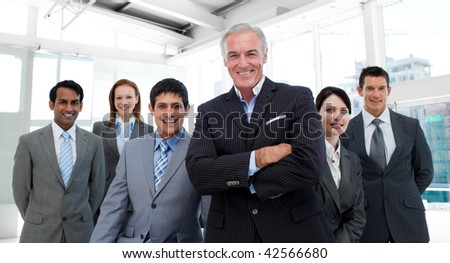 Senior manager with folded arms accompanied by his team in the office - stock photo