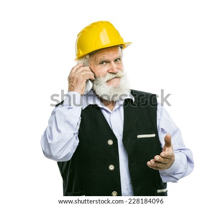 Senior manual worker with yellow helmet calling on the phone isolated over white background - stock photo