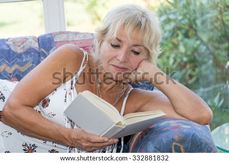 Senior mature blond woman is lying on the couch and reading a book. She looking at the book. All potential trademarks are removed. - stock photo