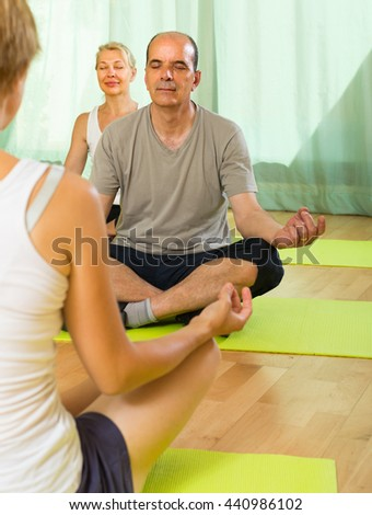 Senior mature couple practicing yoga with female instructor - stock photo