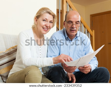 Senior mature couple with financial documents on sofa in home  - stock photo
