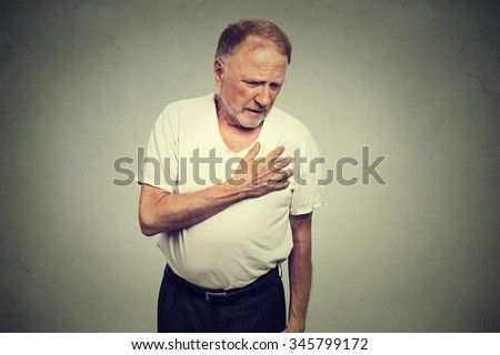 senior mature man suffering from bad pain in his chest heart attack isolated on gray background - stock photo