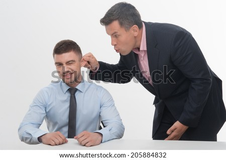 Senior mature manager chief standing by desk pulling his young junior employee ear, isolated on white - stock photo