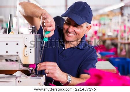 senior mechanic repairing industrial sewing machine in factory - stock photo