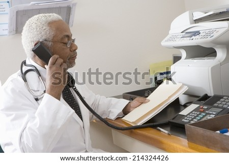 Senior medical practitioner on phone with hospital records