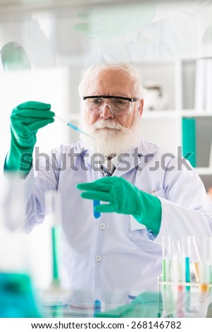 Senior medical scientific researcher filling test-tube